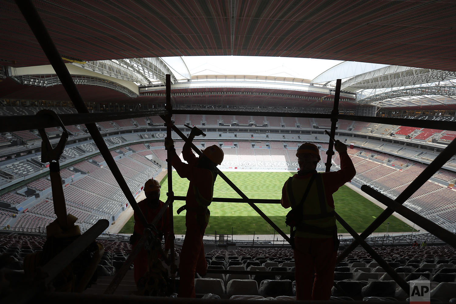 In this Monday, April 29, 2019 photo, labours remove scaffolding at the Al Bayt stadium in Al Khor, about 50 kms, 30 miles, north of Doha, Qatar. (AP Photo/Kamran Jebreili)