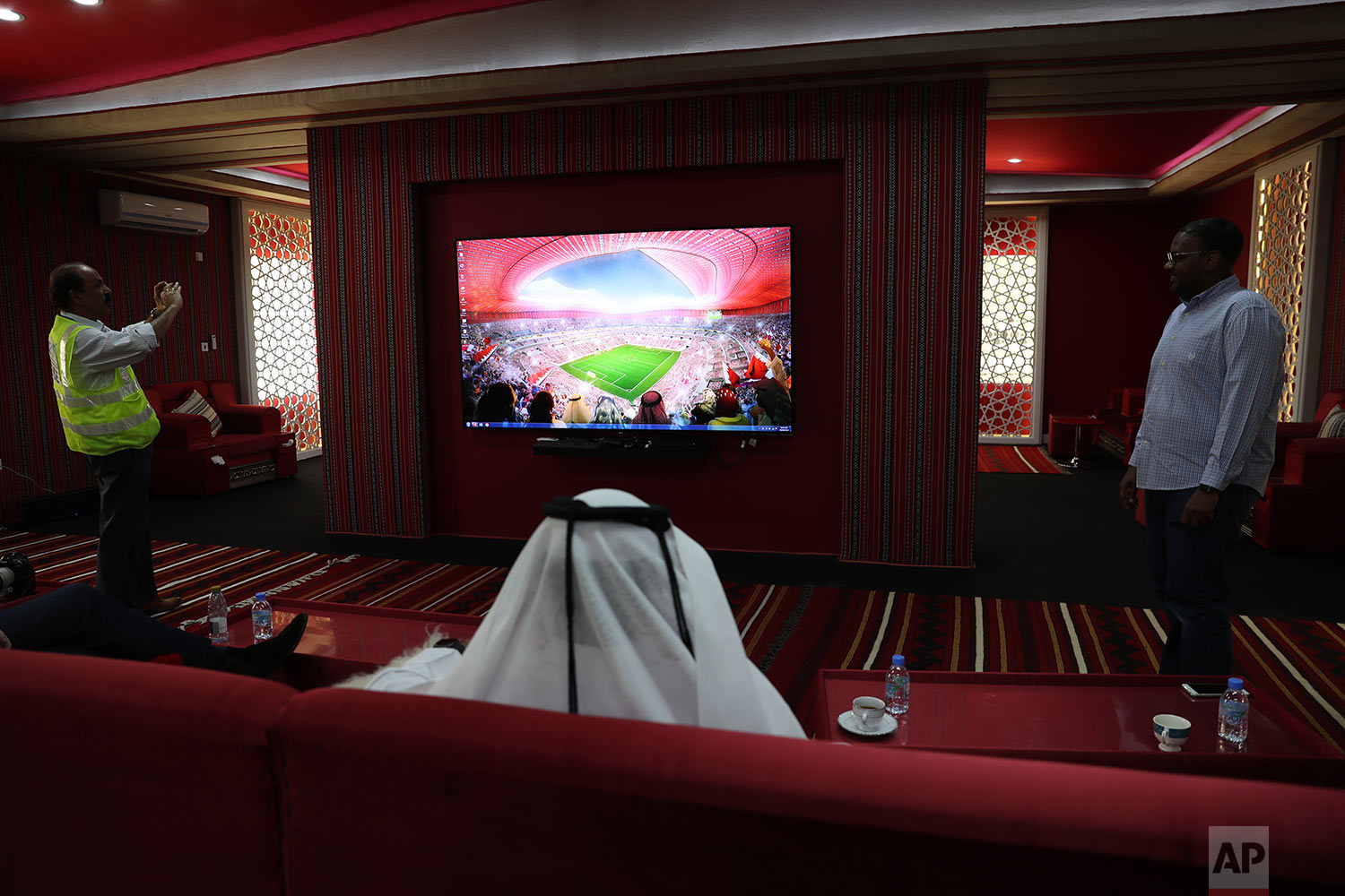 In this Monday, April 29, 2019 photo, visitors watch a presentation ahead of their tour at the Al Bayt stadium in Al Khor, about 50 kms, 30 miles, north of Doha, Qatar. (AP Photo/Kamran Jebreili)