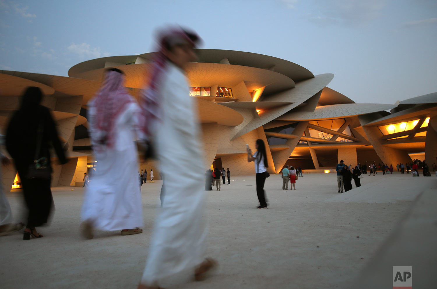 In this Saturday, April 20, 2019 photo, people visit the National Museum of Qatar designed by French architect, Jean Nouvel who got his inspiration from the desert rose crystal and has been opened on March 28th in Doha, Qatar. (AP Photo/Kamran Jebreili)