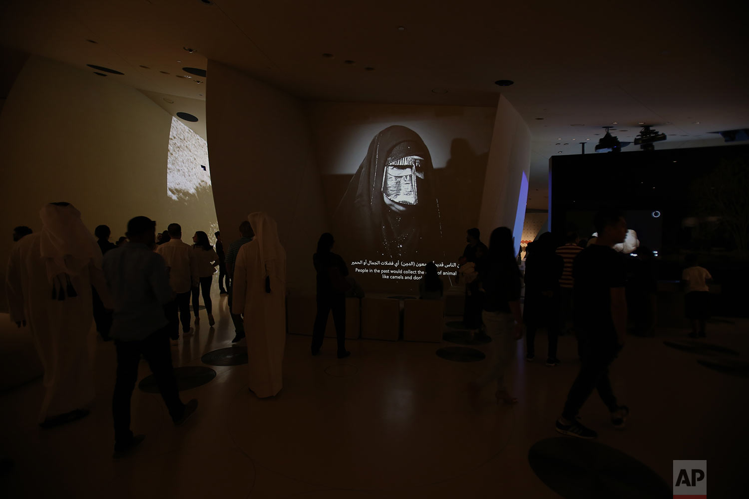 In this Monday, April 22, 2019 photo, people visit one of the galleries with an image of a Qatari woman covered her face with traditional Burqa, at the National Museum of Qatar designed by French architect, Jean Nouvel who got his inspiration from the desert rose crystal and has been opened on March 28th in Doha, Qatar. (AP Photo/Kamran Jebreili)