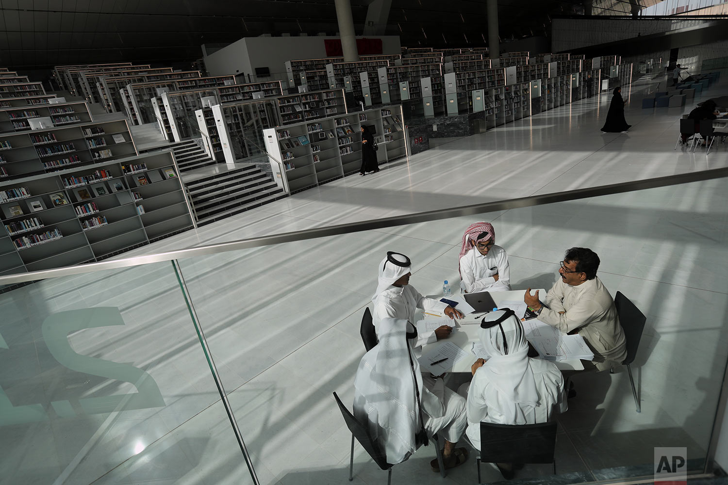 In this Tuesday, April 30, 2019 photo, a few students listen to their professor at the Qatar National Library in Doha, Qatar. (AP Photo/Kamran Jebreili)