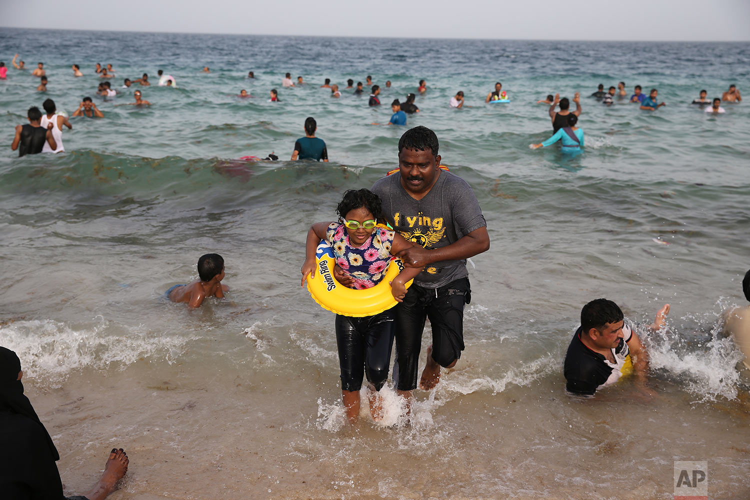 In this Friday, April 19, 2019 photo, a man helps a girl to get out of the water as the people enjoy swimming at the Sealine Beach about 40 kms, 25 miles, south of Doha, Qatar. (AP Photo/Kamran Jebreili)
