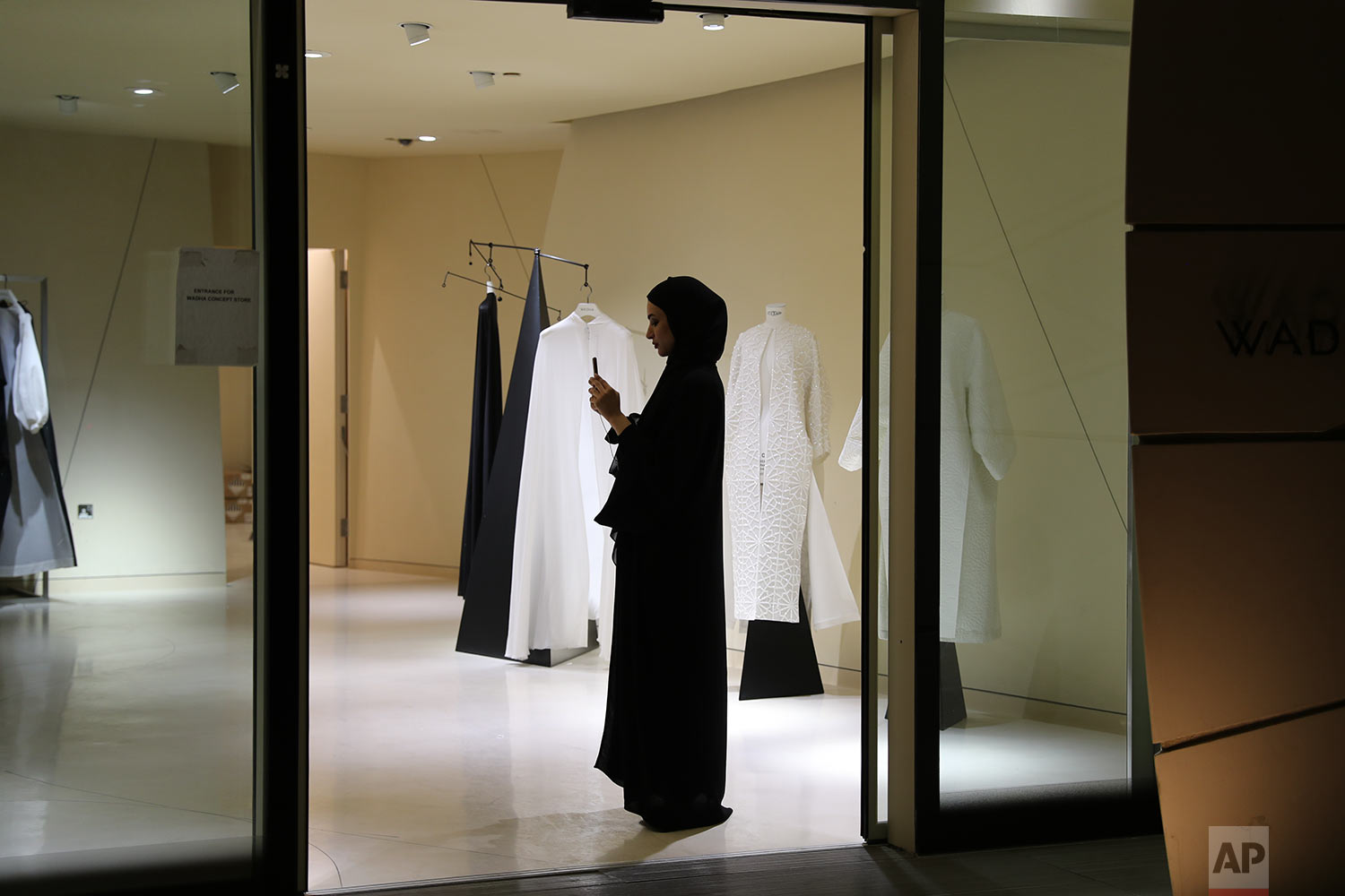 """In this Sunday, April 27, 2019 photo, a woman takes photo with her mobile phone at the """"Wadha Concept Store"""" located at the Qatar National Museum venue in Doha, Qatar. (AP Photo/Kamran Jebreili)"""