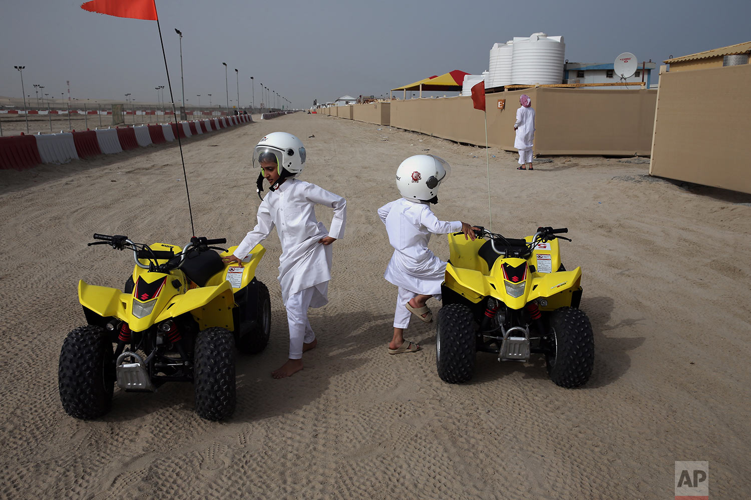 In this Friday, April 19, 2019 photo, two brothers get on their rental dune buggies at a camp by the sealine road, about 40 kms, 25 miles, south of Doha, Qatar. (AP Photo/Kamran Jebreili)