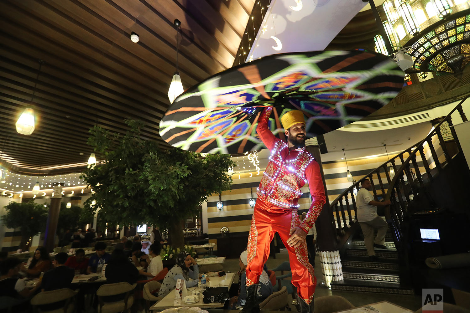 In this Wednesday, May 8, 2019 photo, Egyptian Tanoura dancer, Mustafa Borsho, performs at a restaurant located in Souq Waqif in Doha, Qatar. (AP Photo/Kamran Jebreili)