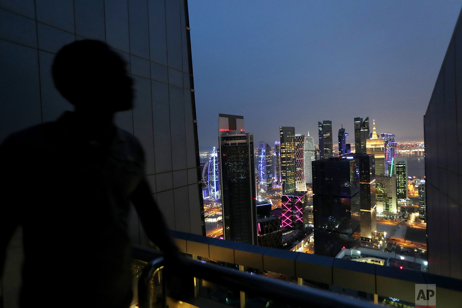In this Saturday, May 4, 2019 photo, a life guard of a hotel swimming pool watches the night view of West Bay district which is the location of many modern high rises in Doha, Qatar. (AP Photo/Kamran Jebreili)