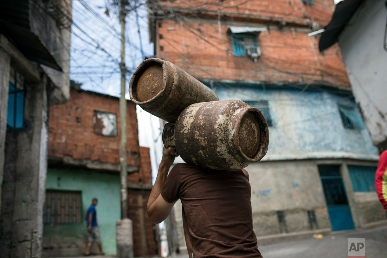 A man carries subsidized gas cylinders provided by the government for 0.13 US dollars in Caracas, Venezuela, Monday, May 13, 2019. (AP Photo/Rodrigo Abd)
