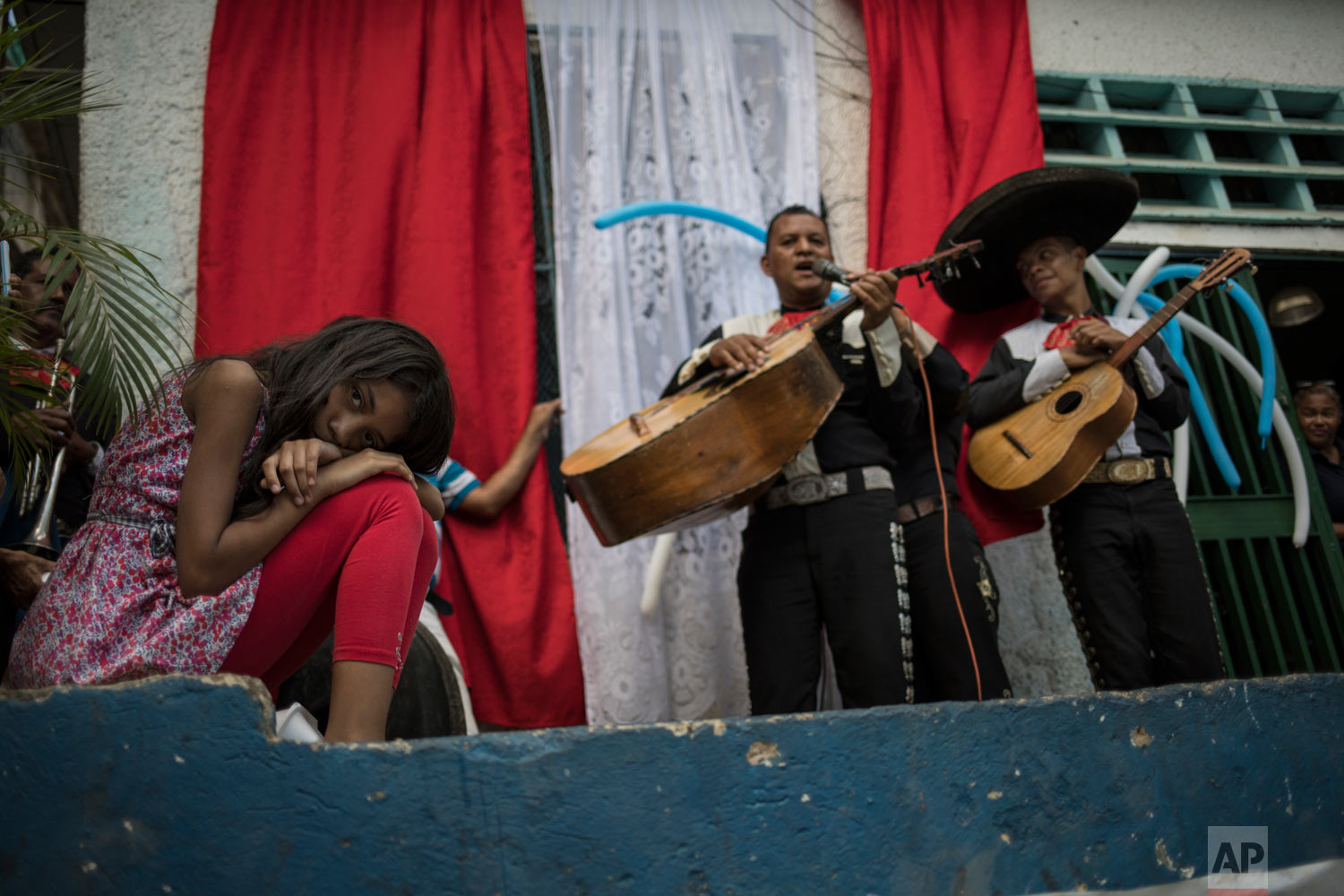A girl lays her head down as she listens to mariachi musicians performing during a Mother's Day block party in Caracas, Venezuela, late Sunday, May 19, 2019. (AP Photo/Rodrigo Abd)