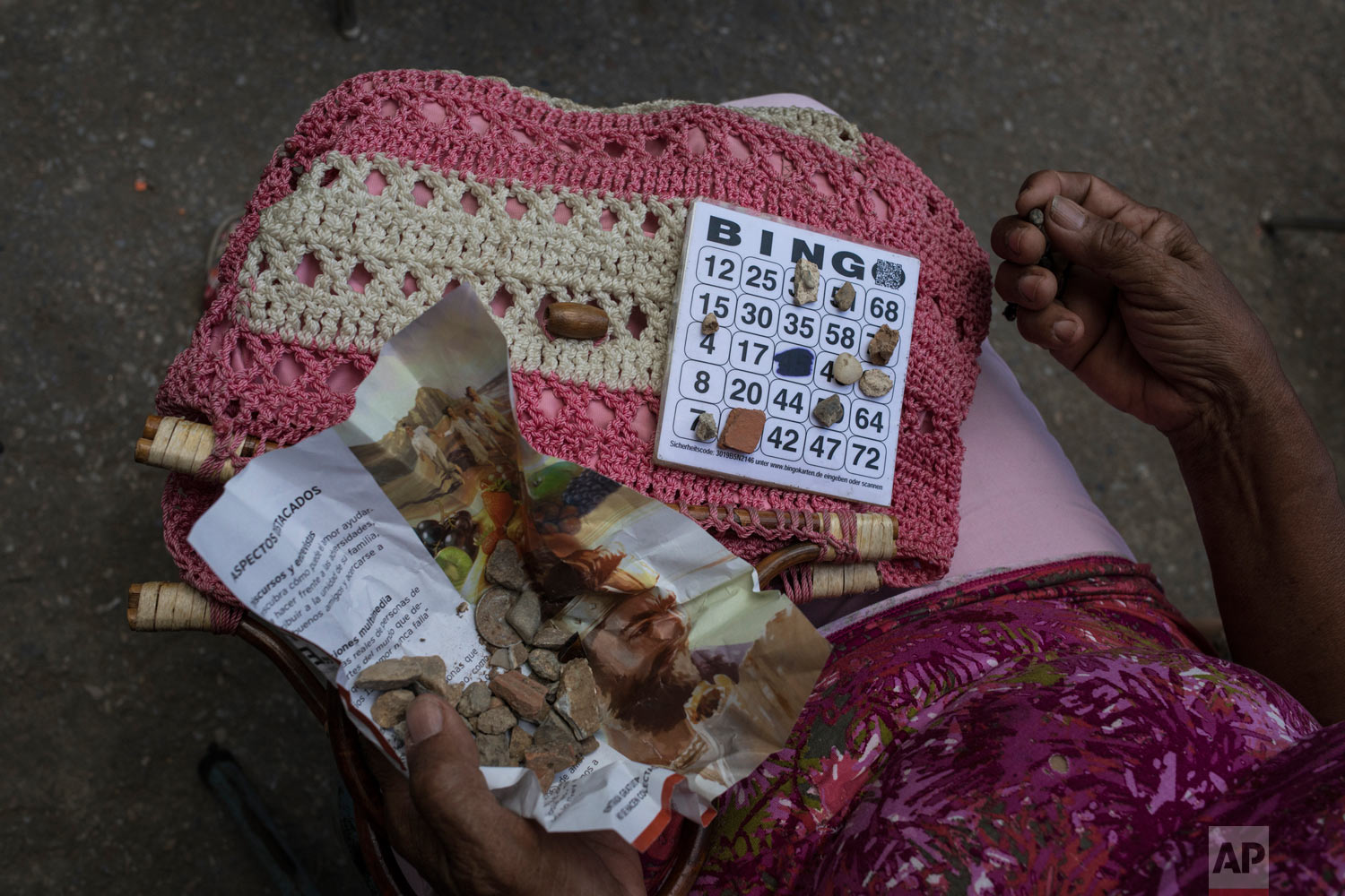 A woman uses pebbles to mark her Bingo card during a Mother's Day block party in Caracas, Venezuela, Sunday, May 19, 2019. (AP Photo/Rodrigo Abd)