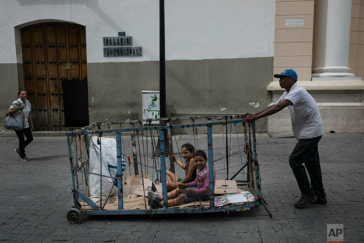 A man pushes his children in his recycling cart through downtown Caracas, Venezuela, Tuesday, May 14, 2019. (AP Photo/Rodrigo Abd)