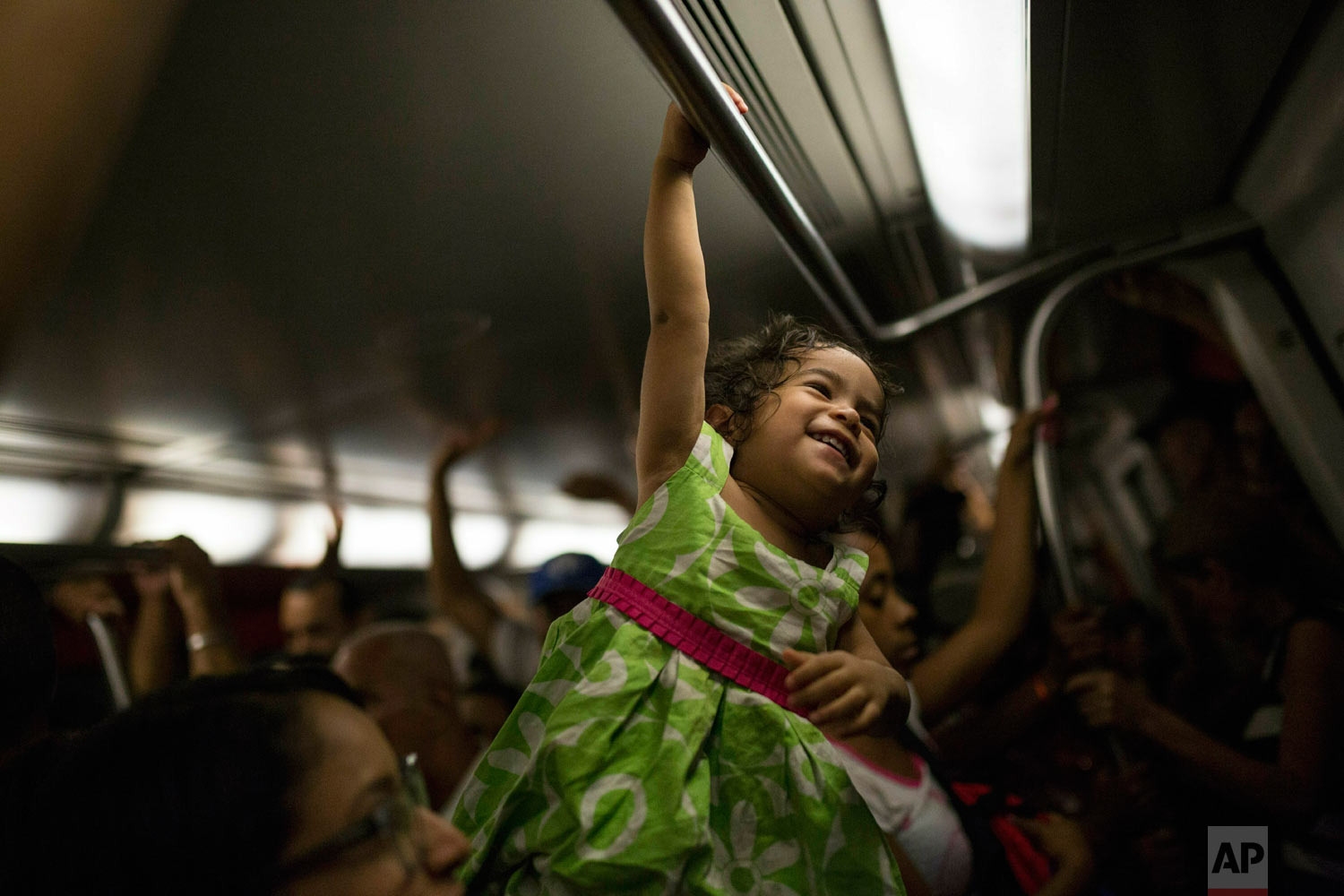 A girl plays while commuting with her mother in the subway in Caracas, Venezuela, Friday, May 10, 2019. (AP Photo/Rodrigo Abd)