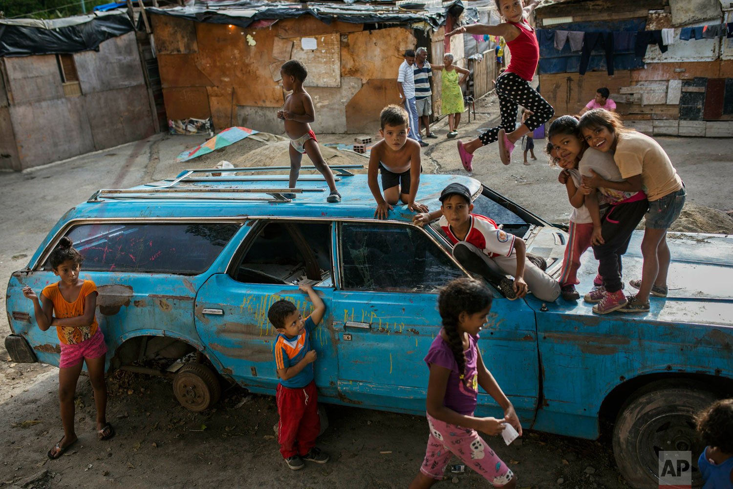 "Children play on top of an abandoned car at the ""Aguerridos Liberator"" shanty town in Caracas, Venezuela, Thursday, May 9, 2019. (AP Photo/Rodrigo Abd)"