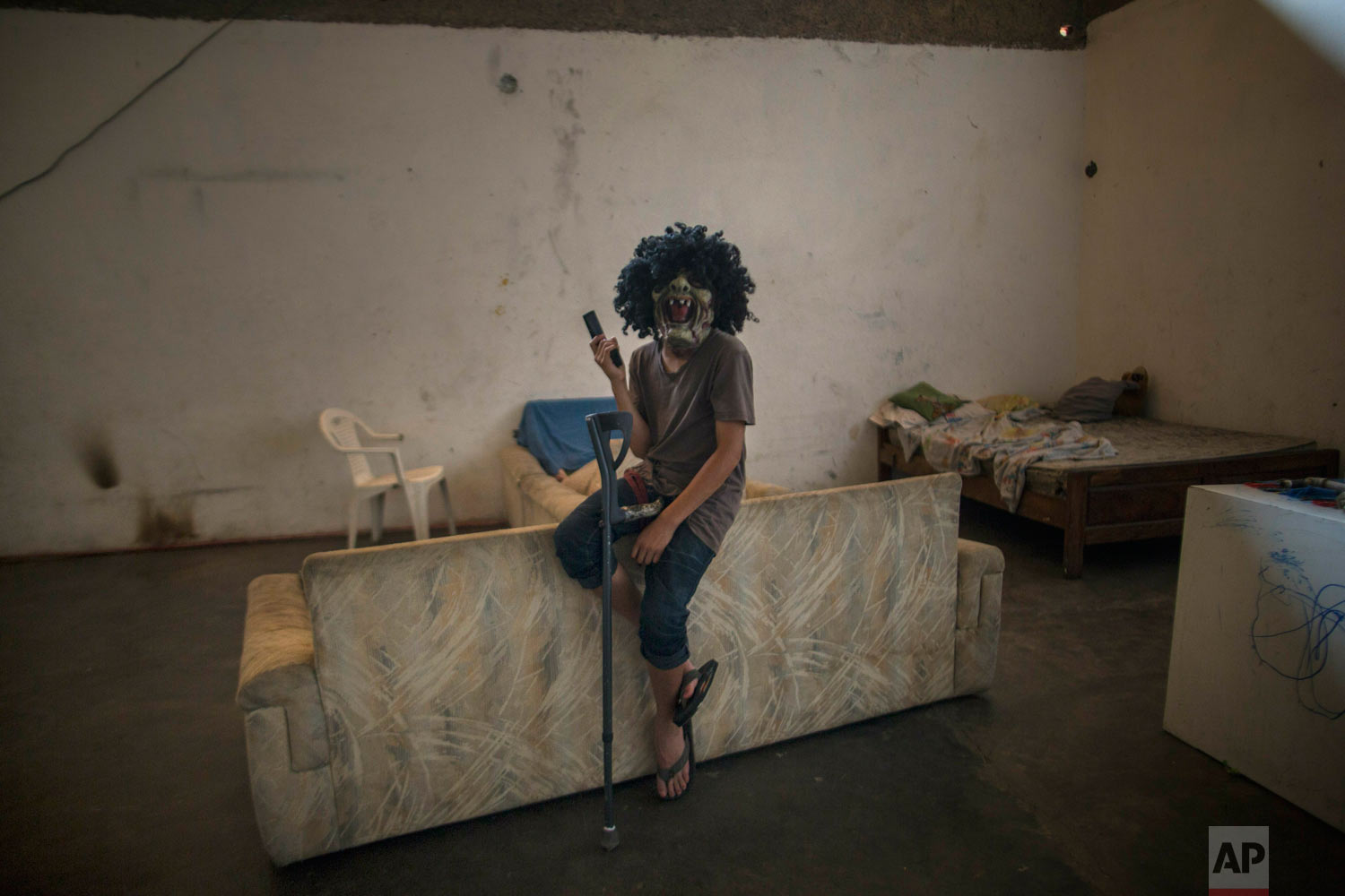 A boy wearing a mask and performing as a gangster with a fake gun, poses for a photo inside a building occupied by squatting families in Caracas, Venezuela, Tuesday, May 7, 2019. (AP Photo/Rodrigo Abd)