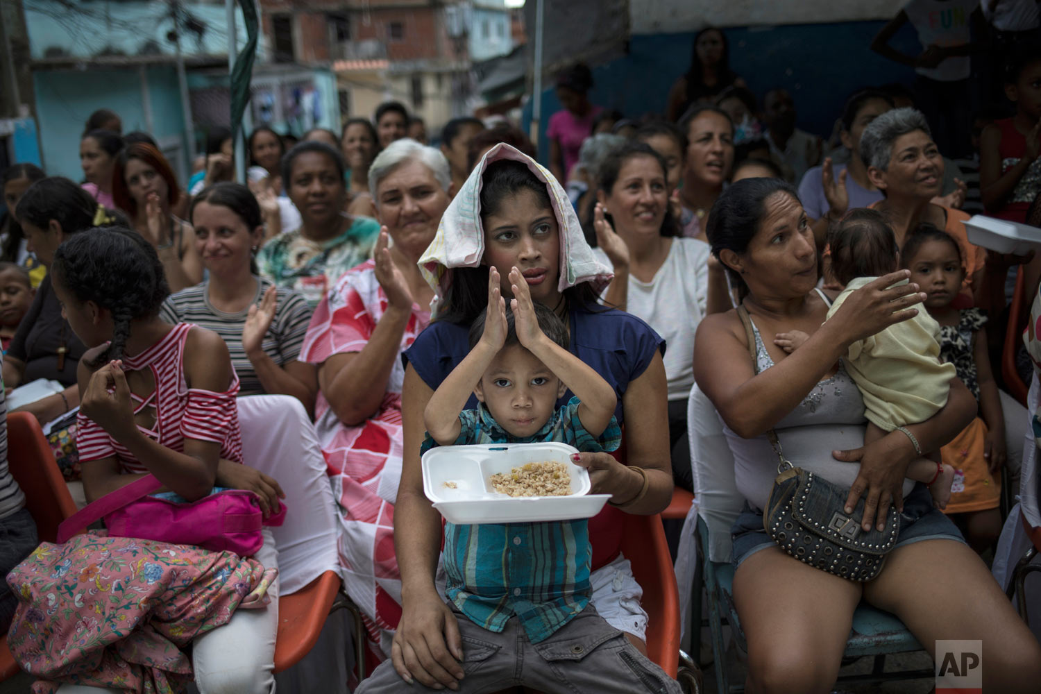 Women watch mariachis musicians perform during a Mother's Day block party in Caracas, Venezuela, late Sunday, May 19, 2019. (AP Photo/Rodrigo Abd)