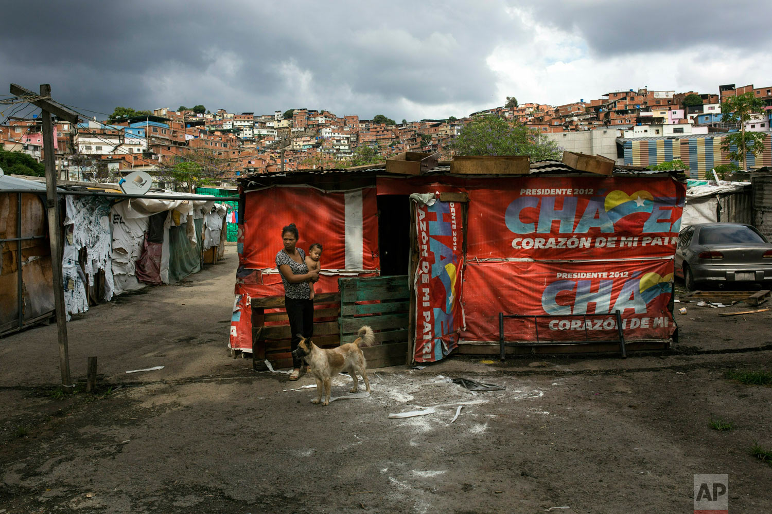 "A woman holds a baby next to her shack in the ""Siembra Socialista"" shanty town, in Caracas, Venezuela, Thursday, May 9, 2019. (AP Photo/Rodrigo Abd)"
