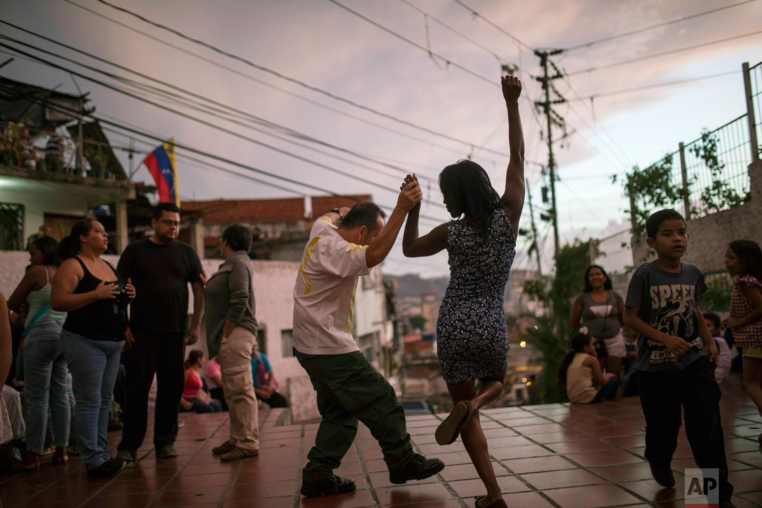 Irene Vaamondez, right, dances with a neighbor as musicians play live music at a public plaza where neighbors socialize in Caracas, Venezuela, at sunset Saturday, May 11, 2019. (AP Photo/Rodrigo Abd)
