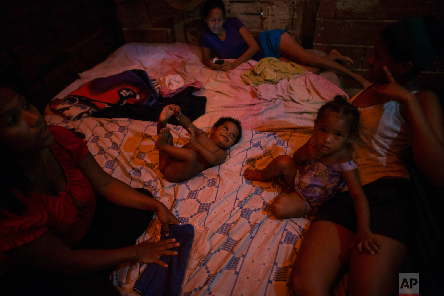 Mothers take care of their children on their room inside a building occupied by squatting families in Caracas, Venezuela, Tuesday, May 7, 2019. (AP Photo/Rodrigo Abd)