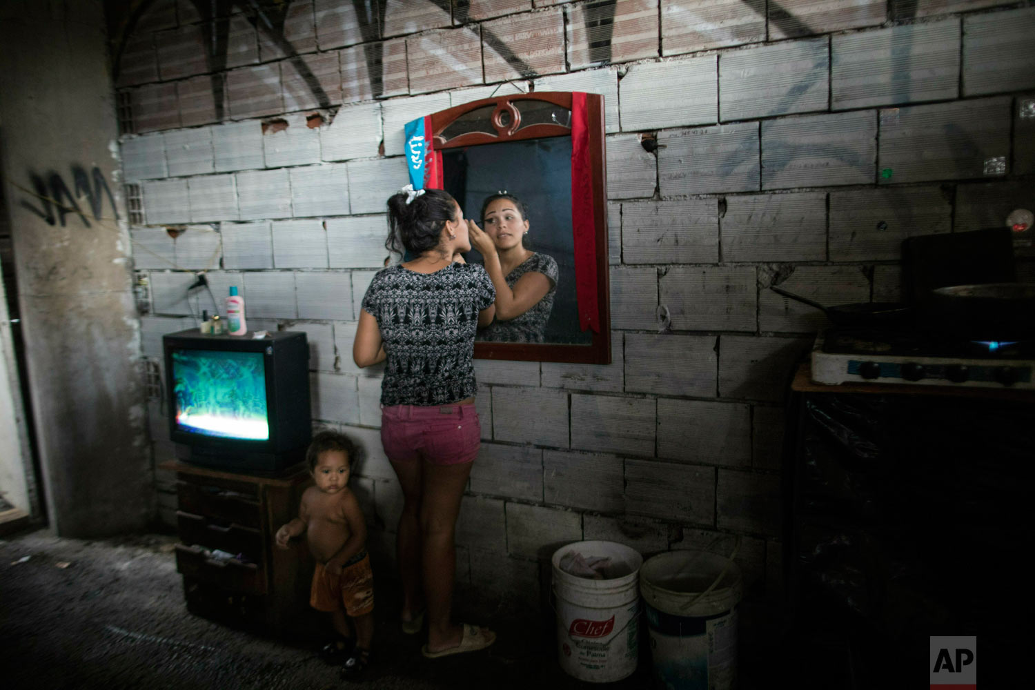 Adriana Rodriguez applies makeup in her room that shares with her three sons and seven other members of other family, in a building occupied by squatting families in Caracas, Venezuela, Monday, May 6, 2019. (AP Photo/Rodrigo Abd)