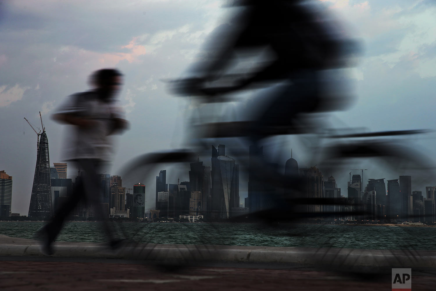 In this Sunday, Feb. 17, 2019 photo, people pass by the city skyline during their early morning workout in Doha, Qatar. (AP Photo/Kamran Jebreili)