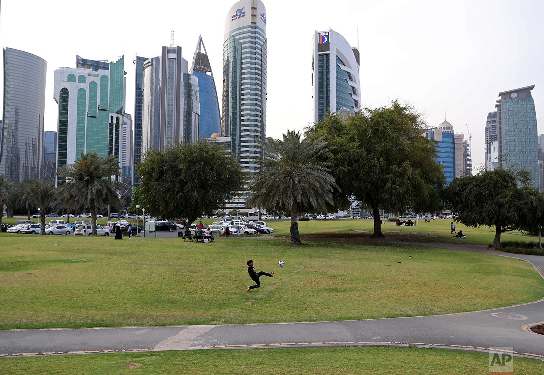 In this Saturday, May 4, 2019 photo, a boy plays football at Dafna park in Doha, Qatar. (AP Photo/Kamran Jebreili)