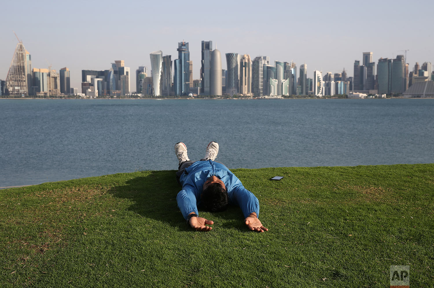 In this Friday, April 19, 2019 photo, a man takes a relax moment on a grass covered hill at the MIA park, overlooking to the skyline of Doha, Qatar. (AP Photo/Kamran Jebreili)
