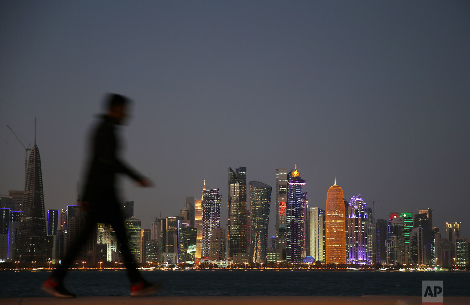 In this Sunday, Feb. 17, 2019 photo, a man passes in front of the city skyline night view in Doha, Qatar. (AP Photo/Kamran Jebreili)