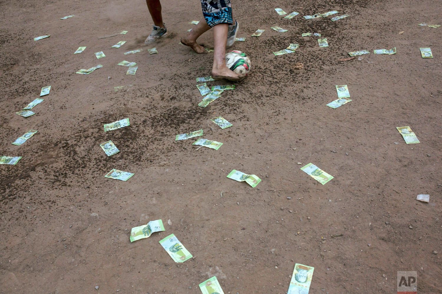 Men play football amid discarded 50 Bolivar bills, outside a building occupied by squatting families in Caracas, Venezuela, Tuesday, May 7, 2019. (AP Photo/Rodrigo Abd)