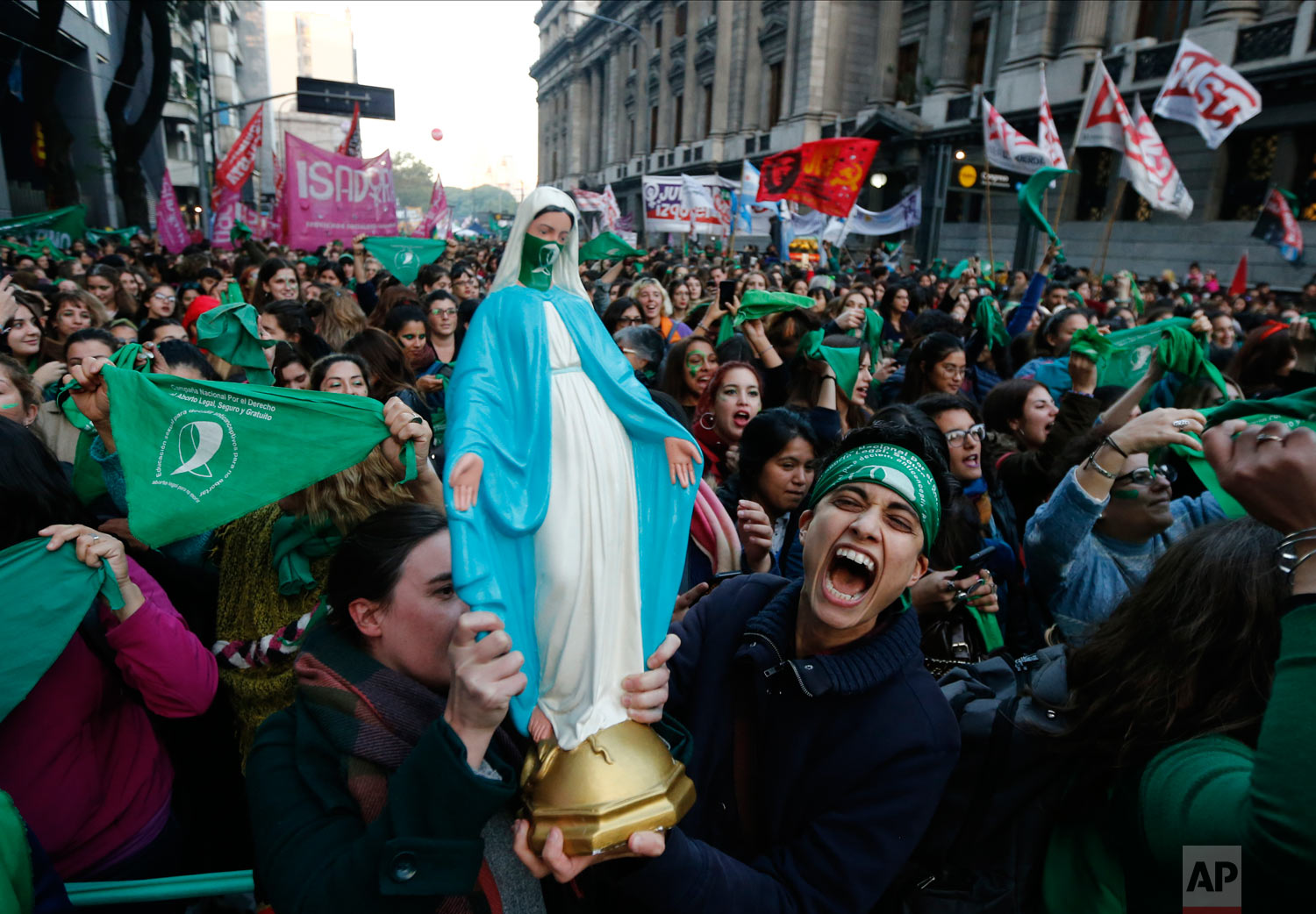 Pro-choice activists carry a statue of the Virgin Mary which features a green handkerchief symbolizing the abortion rights movement in Argentina during a rally outside Congress in favor of legalizing abortion in Buenos Aires, Argentina, Tuesday, May 28, 2019. (AP Photo/Marcos Brindicci)