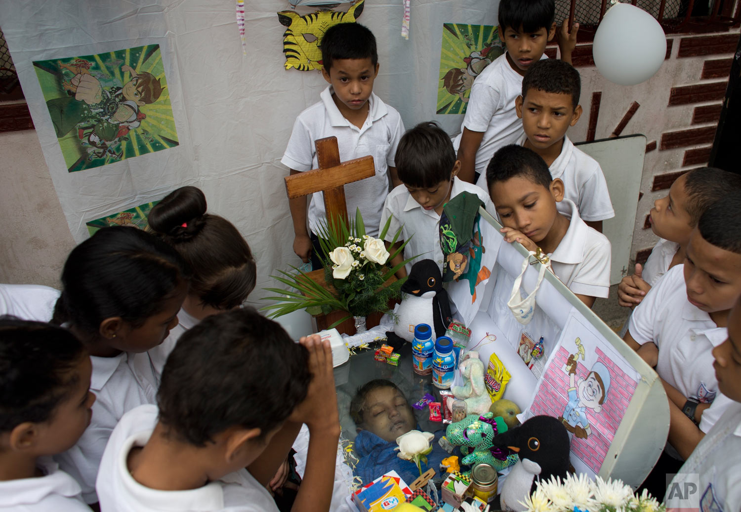 Classmates of 11-year-old Erick Altuve gather around his casket during an outdoor wake near his home in the Petare shantytown of Caracas, Venezuela, Wednesday, May 29, 2019. Erick died on May 26 while he was waiting for a bone marrow transplant. (AP Photo/Ariana Cubillos)