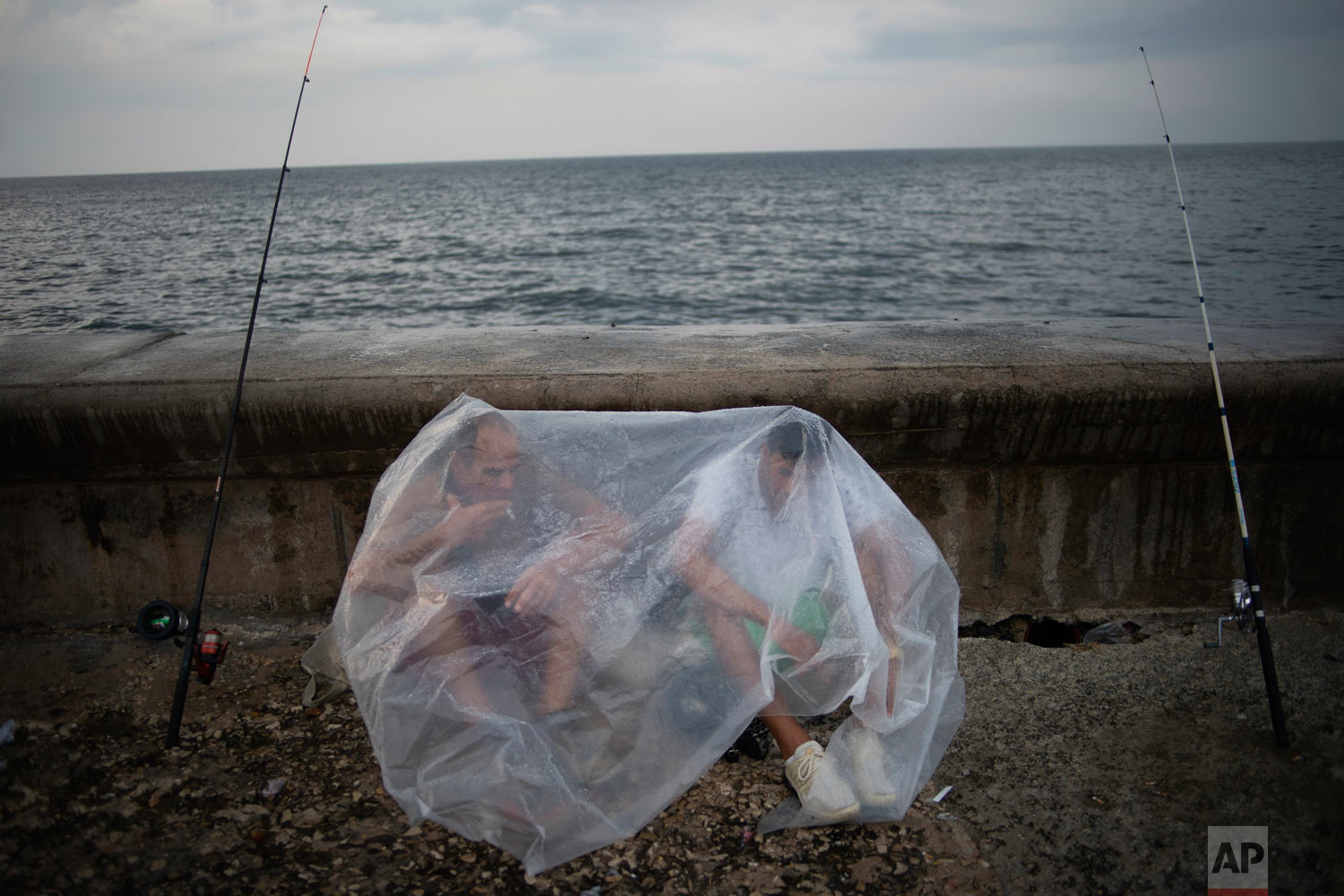 Engelbert Cañete, left, and his friend Ethian Jesus, protect themselves from the rain with a plastic sheet while waiting for the rain to stop so they can continue fishing at the malecón in Havana, Cuba, Monday, May 6, 2019. (AP Photo/Ramon Espinosa)