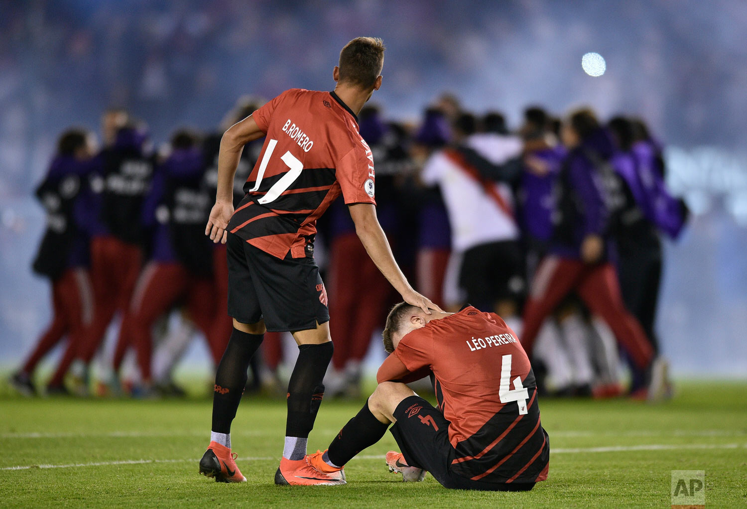 Leo Pereira of Brazil's Athletico Paranaense sits on the field as teammate Braian Romero pats him on the head after they lost the Recopa Sudamericana final 3-0 to Argentina's River Plate in Buenos Aires, Argentina, Thursday, May 30, 2019. (AP Photo/Gustavo Garello)