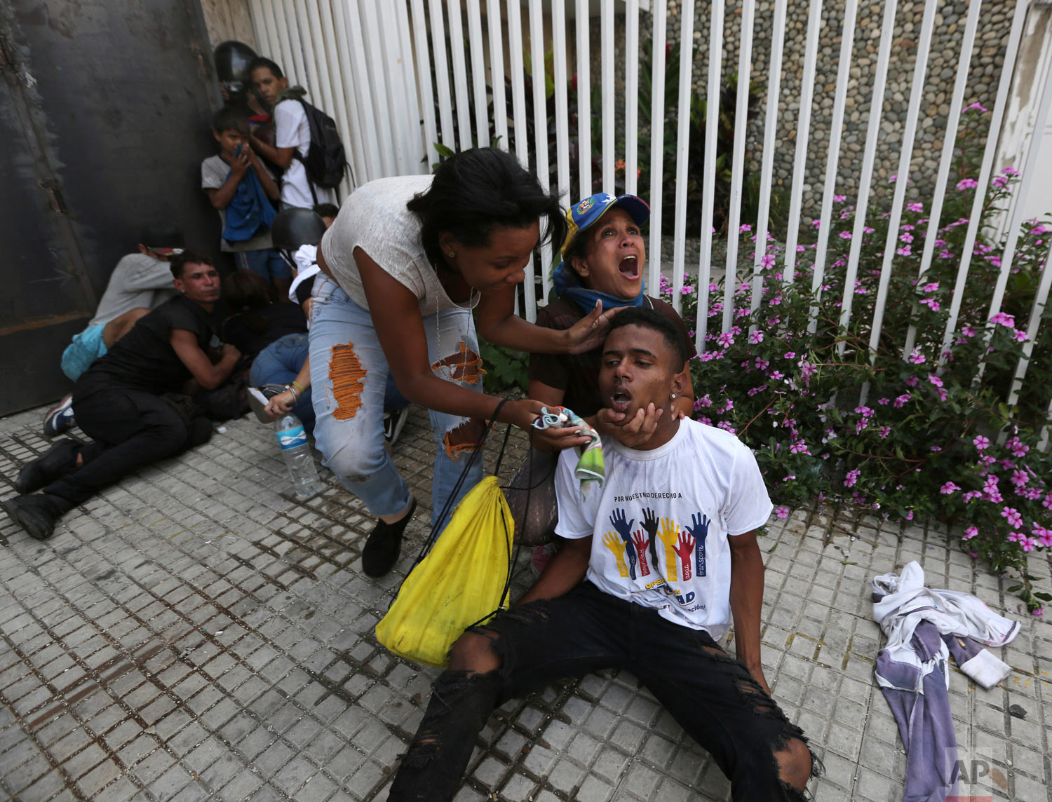 An anti-government protester calls for help as she and another woman help a fellow demonstrator who is overcome by teargas during clashes with security forces in Caracas, Venezuela, Wednesday, May 1, 2019. Opposition leader Juan Guaidó called for Venezuelans to fill streets around the country to demand President Nicolás Maduro's ouster. (AP Photo/Fernando Llano)