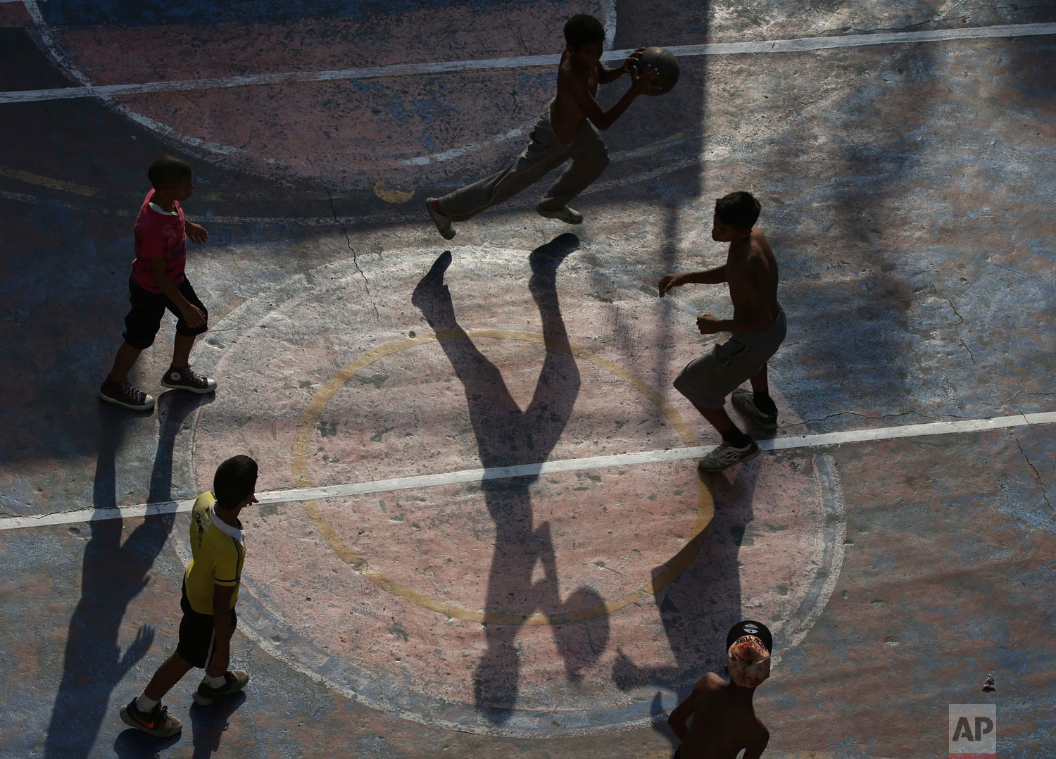 Boys play basketball in the Petare shantytown of Caracas, Venezuela, Thursday, May 16, 2019. (AP Photo/Martin Mejia)