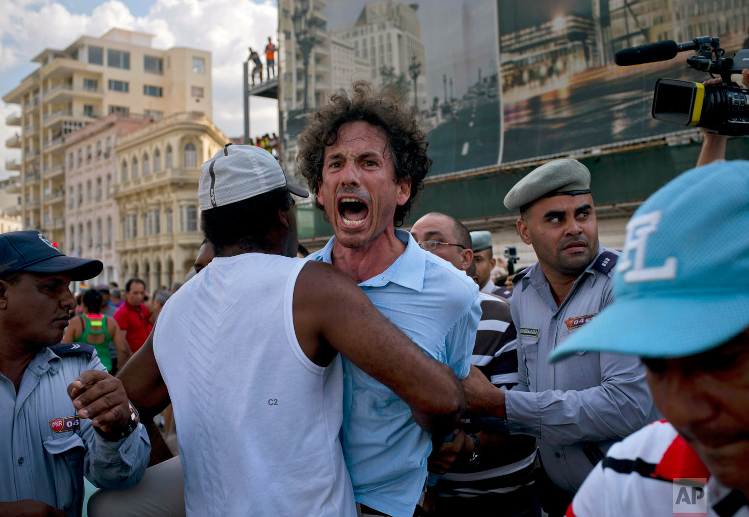 Cuban police detain a gay rights activist during an unauthorized march in Havana, Cuba, Saturday, May 11, 2019.  The march was organized largely using Cuba's new mobile internet, with gay-rights activists and groups of friends calling for a march over Facebook and WhatsApp after the government-run gay rights organization cancelled a march. (AP Photo/Ramon Espinosa)