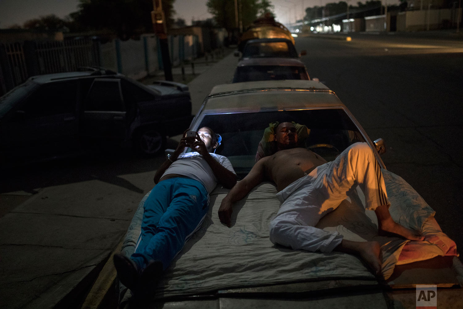Andres Quintero, left, and Fermin Perez rest on top of Perez's car as they wait in line for over 20 hours to fill their tanks with gas in Cabimas, Venezuela, Thursday, May 16, 2019. U.S. sanctions on oil-rich Venezuela resulyrf in mile-long lines for fuel in the South American nation. (AP Photo/Rodrigo Abd)