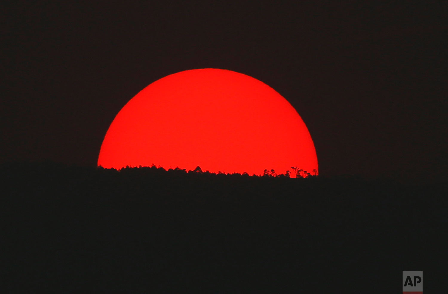 Tinted blood red by a thick cloud of smoke and pollution, the sun sets on the mountains above Mexico City, Monday, May 13, 2019. (AP Photo/Marco Ugarte)