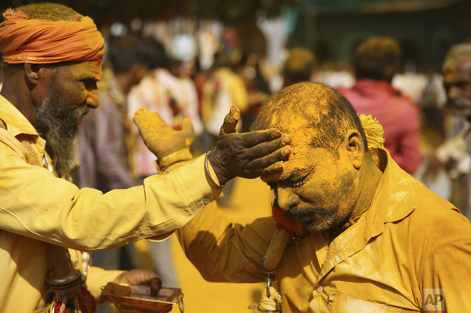 A devotee applies the spice turmeric during the celebration of the Bhandara Festival, or the Festival of Turmeric, at the Jejuri temple in Pune district, Maharashtra state, India, Monday, June 3, 2019. (AP Photo/Rafiq Maqbool)