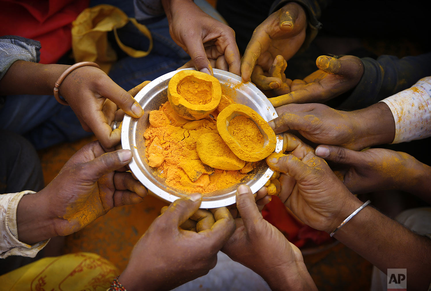 Devotees hold a plate with turmeric as they offer prayers during the celebration of the Bhandara Festival, or the Festival of Turmeric, at the Jejuri temple in Pune district, Maharashtra state, India, Monday, June 3, 2019. (AP Photo/Rafiq Maqbool)