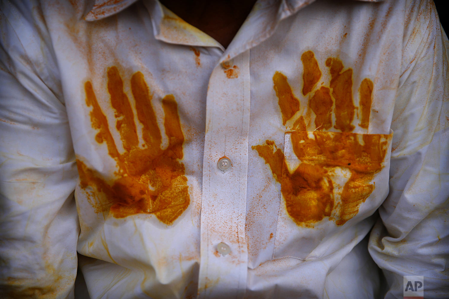 A devotee's shirt has handprints of the spice turmeric during the celebration of the Bhandara Festival, or the Festival of Turmeric, at the Jejuri temple in Pune district, Maharashtra state, India, Monday, June 3, 2019. (AP Photo/Rafiq Maqbool)