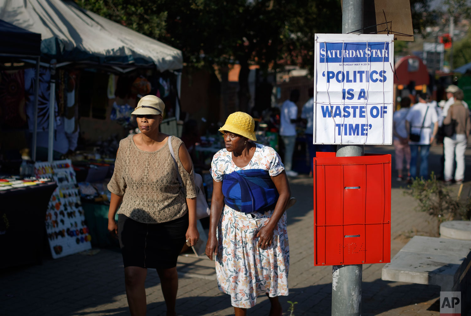 Two women walk past a placard carrying a headline from the Saturday Star newspaper, in Soweto township, Johannesburg, South Africa Saturday, May 4, 2019.  (AP Photo/Ben Curtis)