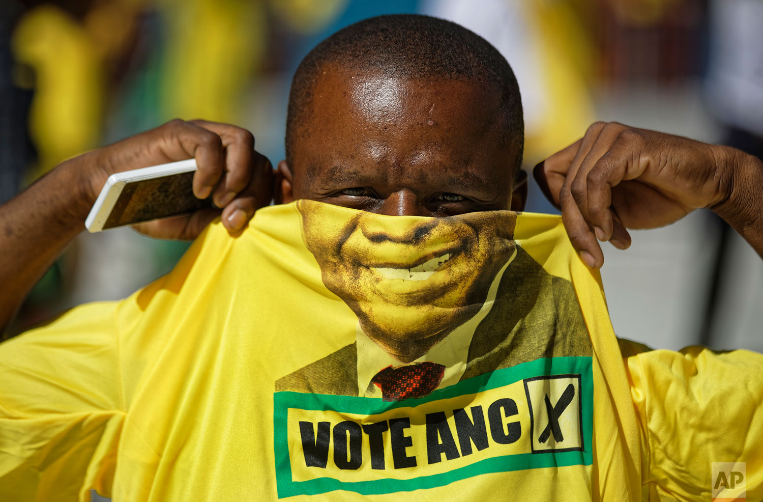 A supporter of the ruling African National Congress (ANC) holds up a t-shirt of President Cyril Ramaphosa as he attends their final election rally at Ellis Park stadium in Johannesburg, South Africa Sunday, May 5, 2019.  (AP Photo/Ben Curtis)