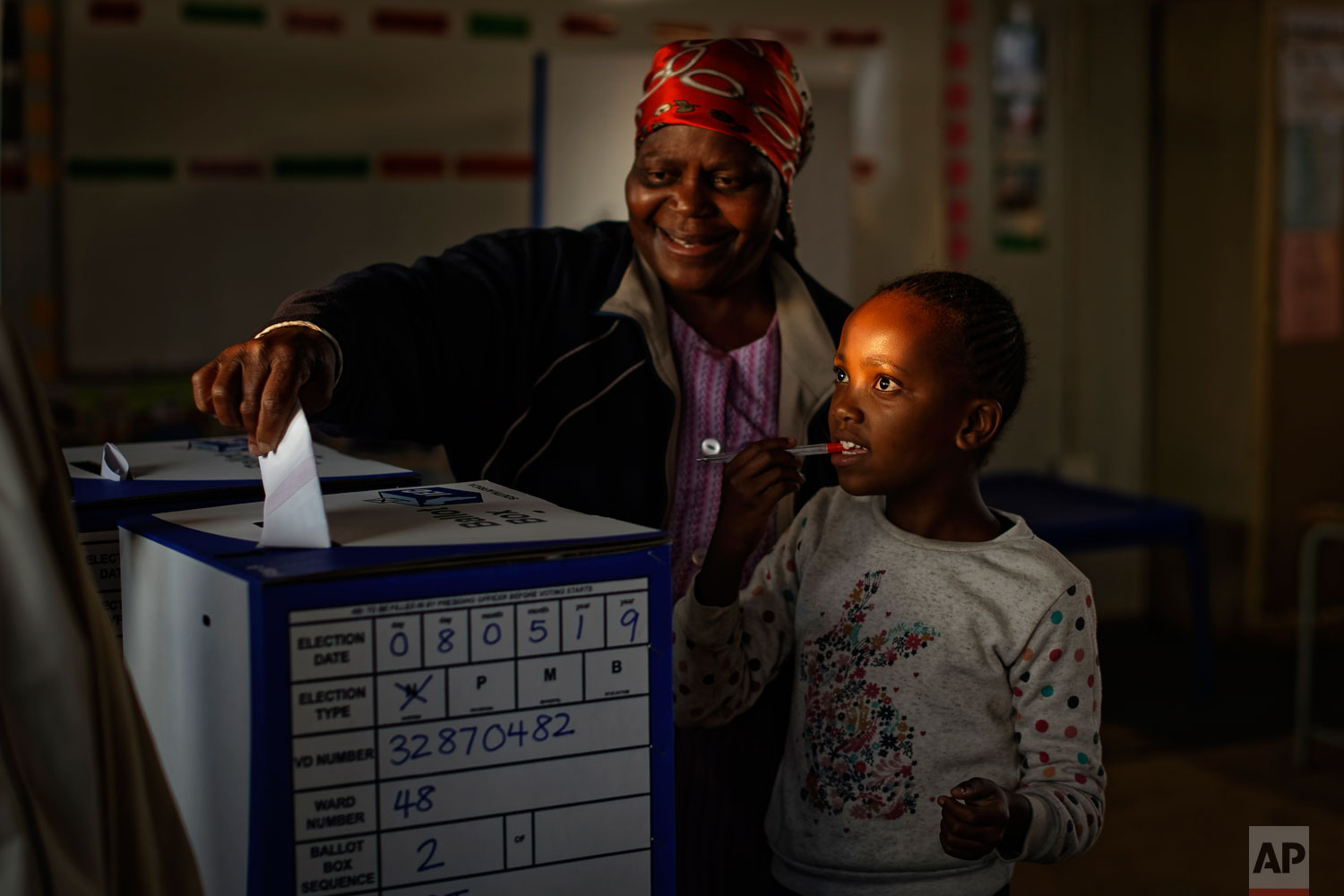 A young girl accompanies a relative as she casts her vote at the end of the day at a polling station in Dobsonville, Johannesburg, South Africa Wednesday, May 8, 2019.  (AP Photo/Ben Curtis)