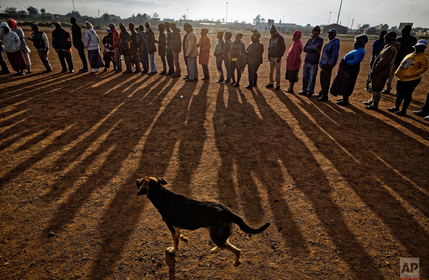 South Africans queue in the early morning sun to cast their votes in the mining settlement of Bekkersdal, west of Johannesburg, in South Africa Wednesday, May 8, 2019. (AP Photo/Ben Curtis)