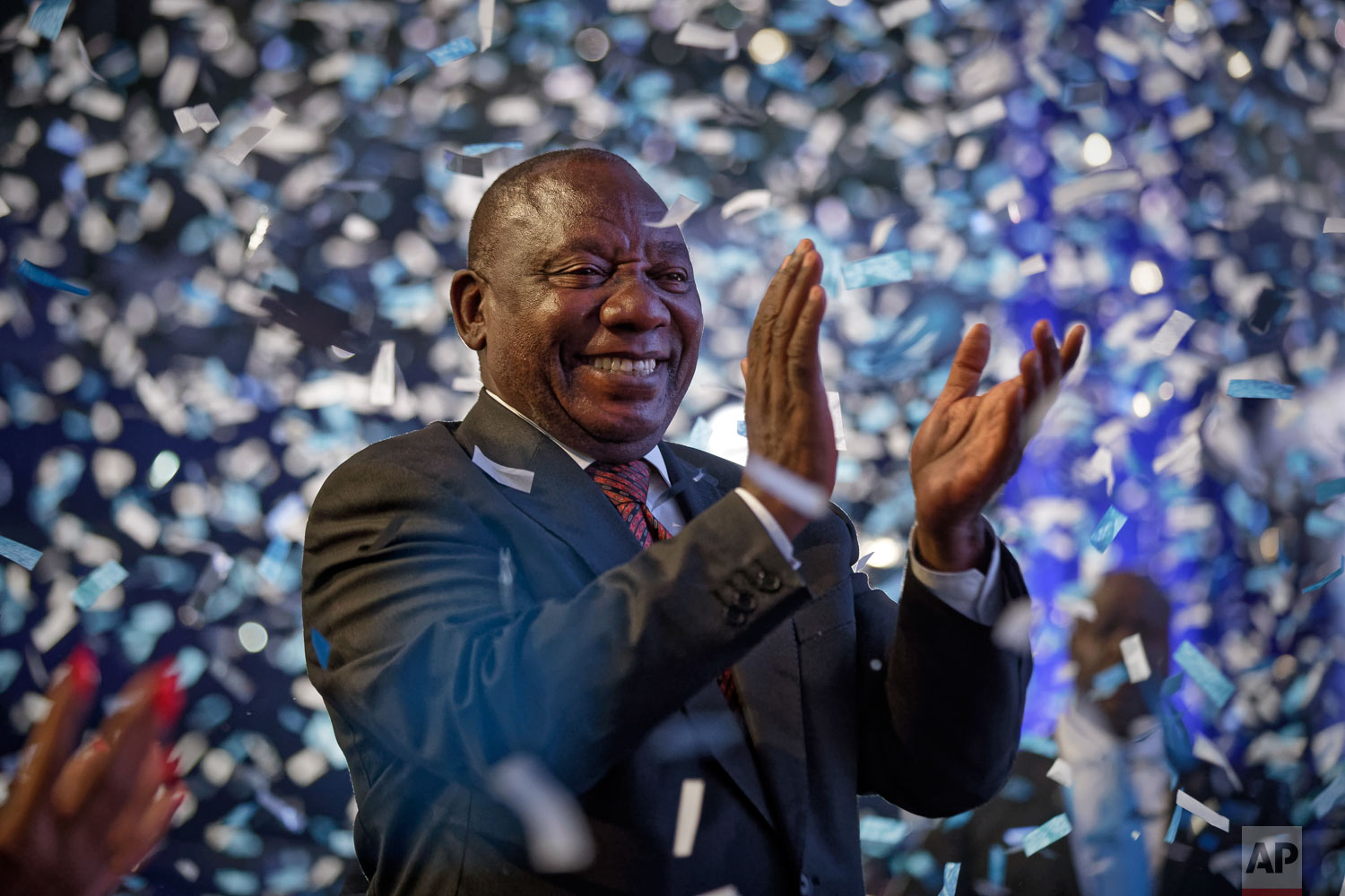 President Cyril Ramaphosa applauds as confetti is launched at the end of the results ceremony at the Independent Electoral Commission Results Center in Pretoria, South Africa Saturday, May 11, 2019.  (AP Photo/Ben Curtis)