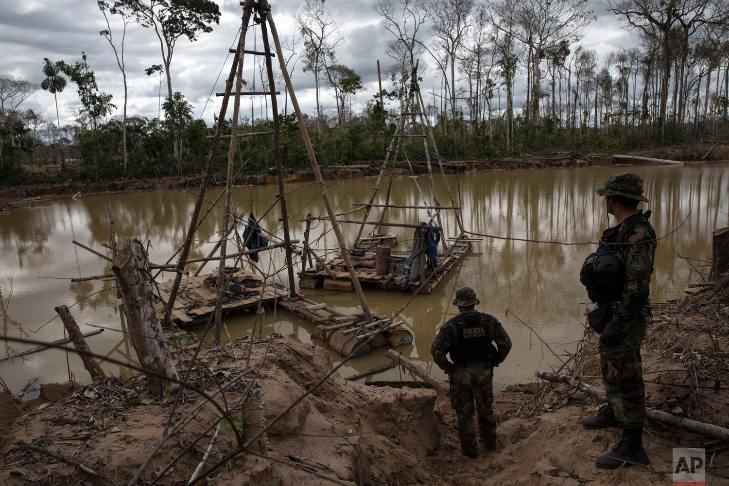 "In this April 1, 2019 photo published May 15, police special forces stand next to illegal mining machinery in Peru's Tambopata province. As part of ""Operation Mercury"", Peruvian police and soldiers search for and destroy equipment used by illegal gold miners in a part of the Amazon rainforest where the mining transformed dense foliage into a desert pocked with dead trees and toxic pools. (AP Photo/Rodrigo Abd)"
