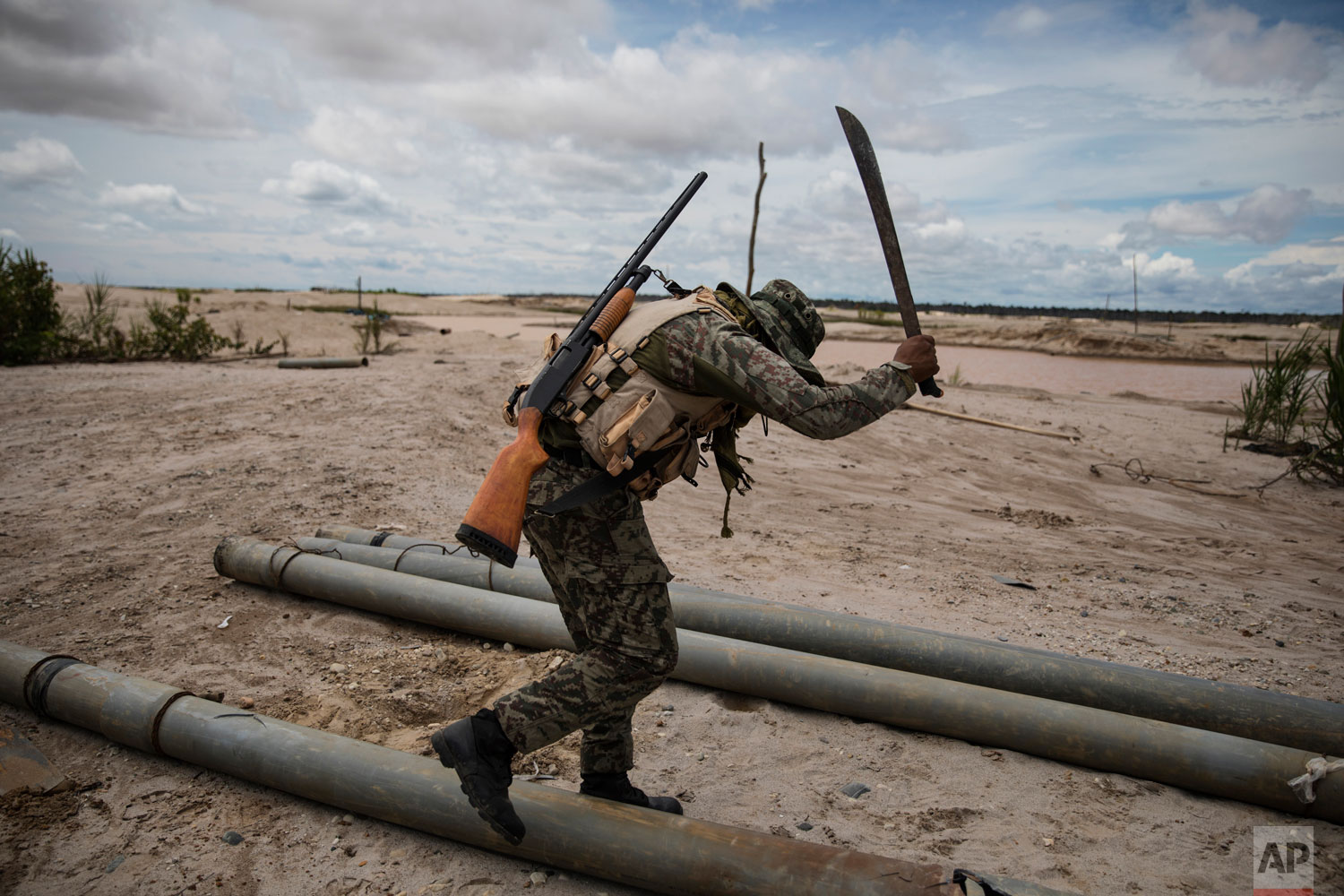 "In this March 27, 2019 photo published May 15, a soldier hacks with a machete tubing used by illegal miners to mine gold, as part of ""Operation Mercury"", in Peru's Tambopata province. The police and soldiers occasionally find machinery used by the illegal miners, and blow it up with dynamite. They also destroy metal tubing used to mine gold. (AP Photo/Rodrigo Abd)"