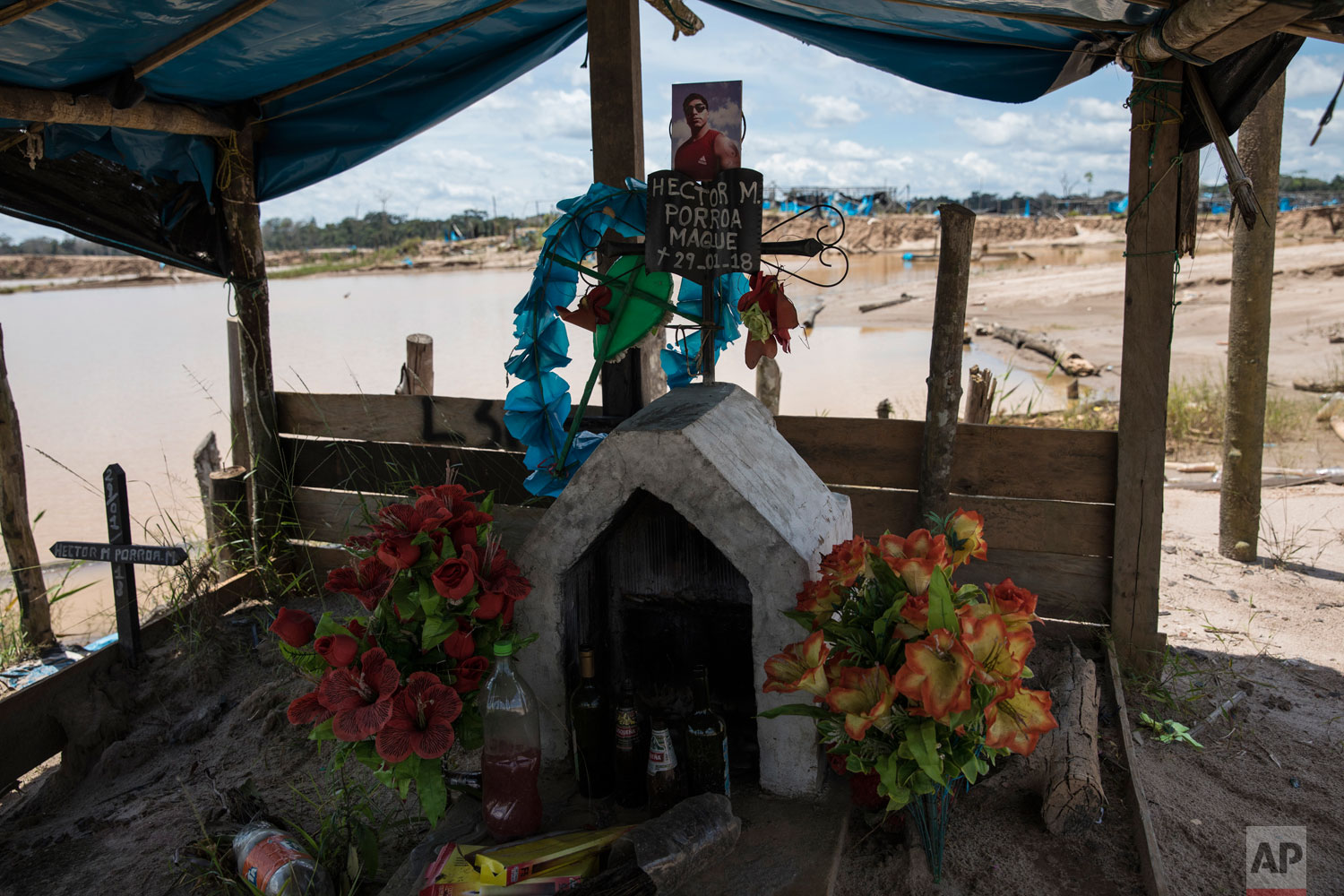 "This March 28, 2019 photo published May 15 shows a memorial adorned with artificial flowers and bottles of alcohol inside a former illegal gold mining camp that has been occupied by ""Operation Mercury"" special forces and converted into the Balata police and military base, in Peru's Tambopata province.  Ernesto Ráez, a biology professor in the Peruvian capital of Lima, said it will take generations to restore and reforest areas affected by mining. (AP Photo/Rodrigo Abd)"