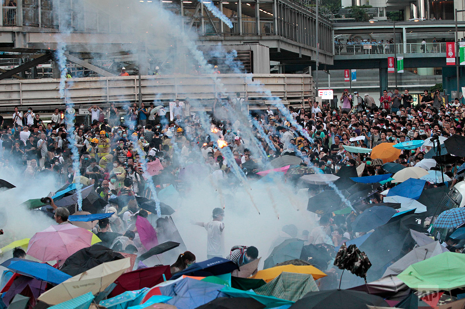 Riot police launch tear gas into the crowd as thousands of protesters surround the government headquarters in Hong Kong, Sept. 28, 2014. (AP Photo/Wally Santana)