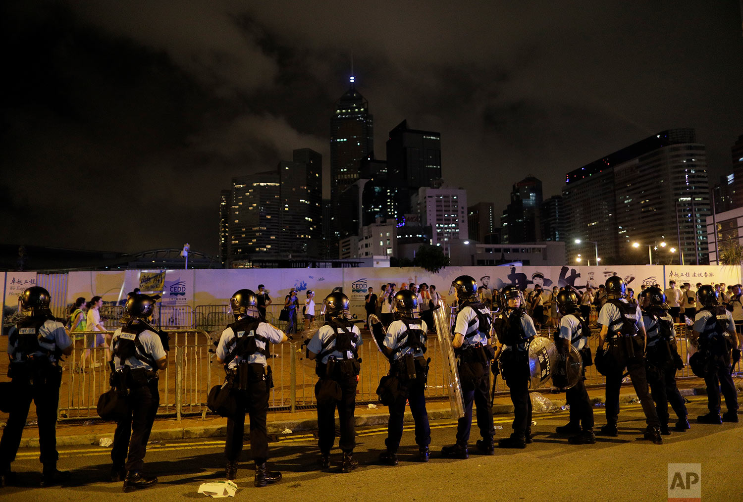 Police officers stand guard against protesters in a rally against the proposed amendments to the extradition law at the Legislative Council in Hong Kong during the early hours of Monday, June 10, 2019. (AP Photo/Vincent Yu)