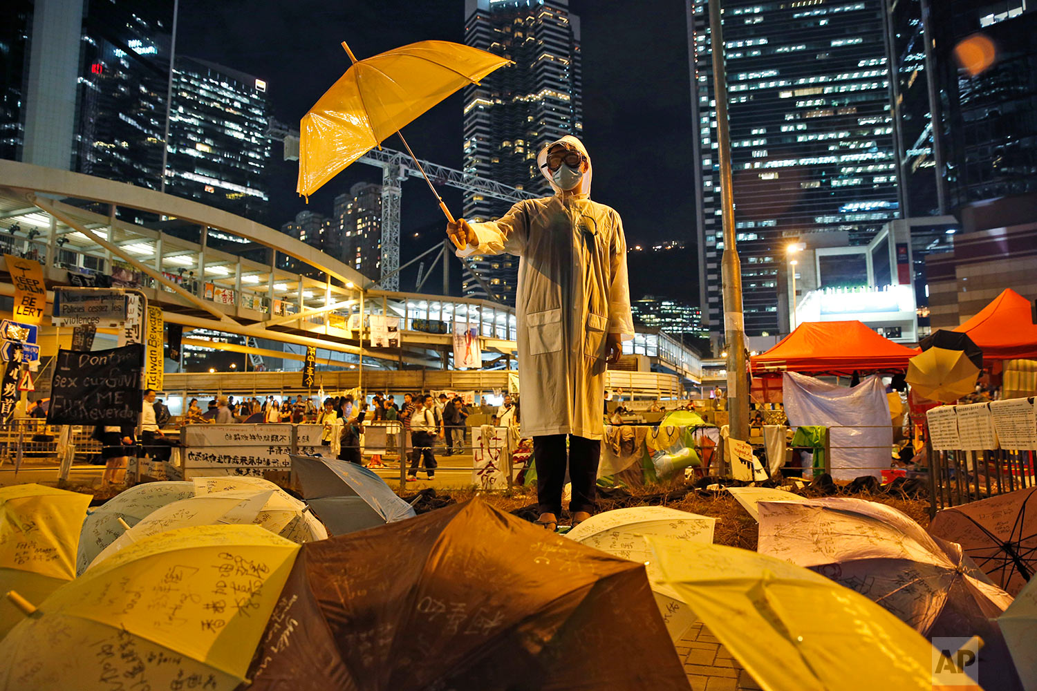 A protester holds an umbrella during a performance on a main road in the occupied areas outside government headquarters in Hong Kong's Admiralty, Oct. 9, 2014. (AP Photo/Kin Cheung)